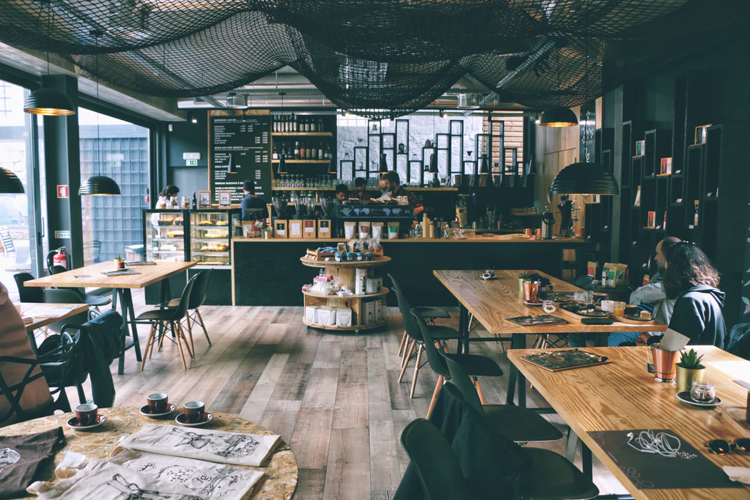 Coffee shop with wooden floors and tables, netting hanging from ceiling